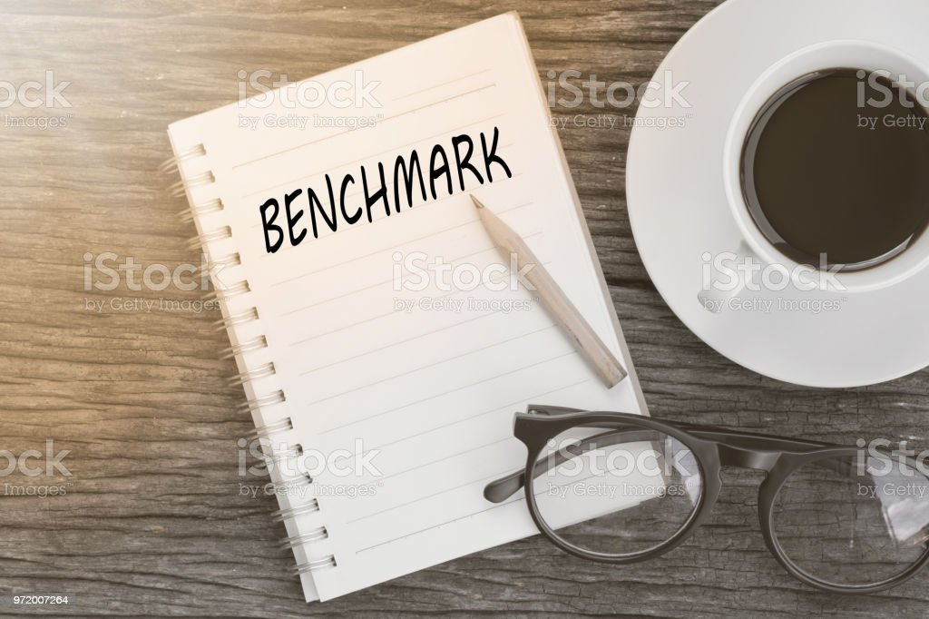 Benchmark concept on notebook with glasses, pencil and coffee cup on wooden table. Business concept. stock photo