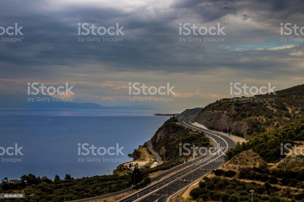 bend road snakelike clouds and ocean stock photo