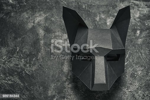 bending cardboard black wolf mask on a black background, top view with copy space