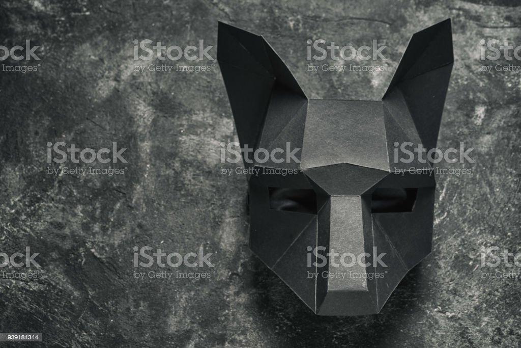dobra a máscara de papelão lobo negro sobre um fundo preto, vista superior com espaço de cópia - foto de acervo