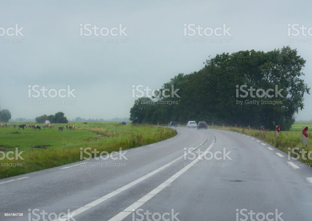 Bending country road in wet weather stock photo