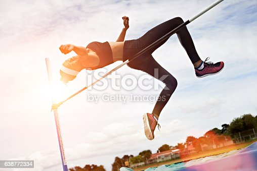 Shot of a young woman in mid air doing a high jump on a sports field
