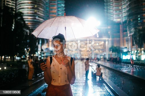 Young woman - solo traveler - enjoying her time in Malaysia, traveling and sightseeing. As the night falls, she is passing by the famous Twin towers, checking on her cellphone, looking on the map where to go next, or just taking a break to upload an image or two.