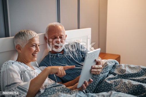 A senior couple entertaining themselves in bed with a tablet, while also sharing an earphone each.