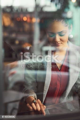 Cropped shot of a young businesswoman using a digital tablet in a cafe