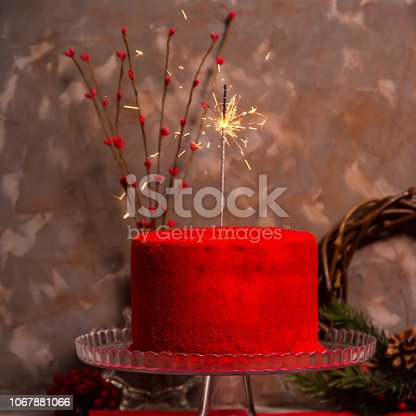 istock Bengal fire burning on a beautiful red velvet birthday cake on a glass stand against a gray dark background. Christmas dessert 1067881066