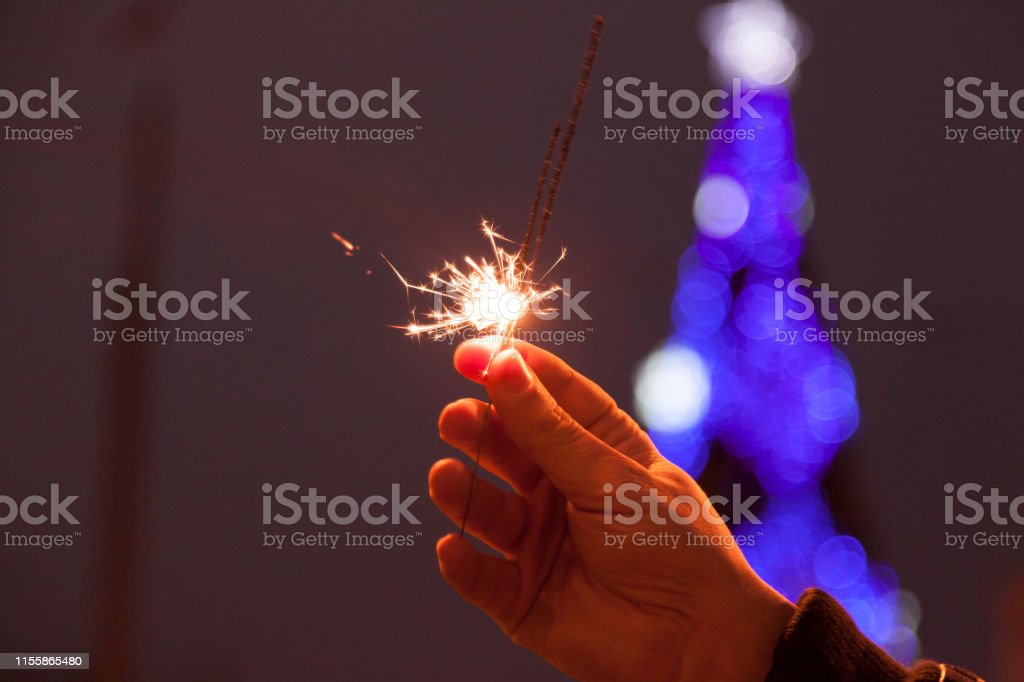 Sparklers burn in male hands against backdrop of burning urban...