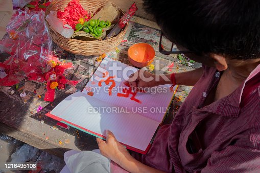 Kalighat, Kolkata, West Bengal, India - April 15th 2019 : Hindu priest drawing auspicious religious signs, on front pages of new accounts book for starting Bengali new year. Bengali Hindu ritual.