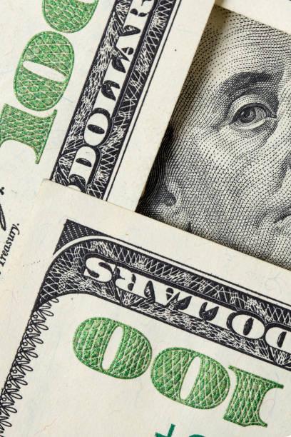Benjamin Franklin looking from $100 bills stock photo