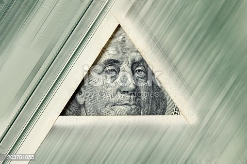 Triangle made of $100 banknotes with Benjamin Franklin portrait inside. Motion blur effect.