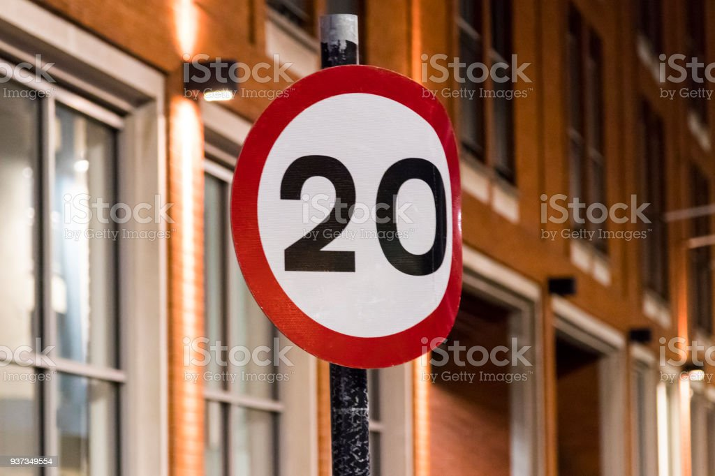 Bent 20mph sign on a street at night stock photo