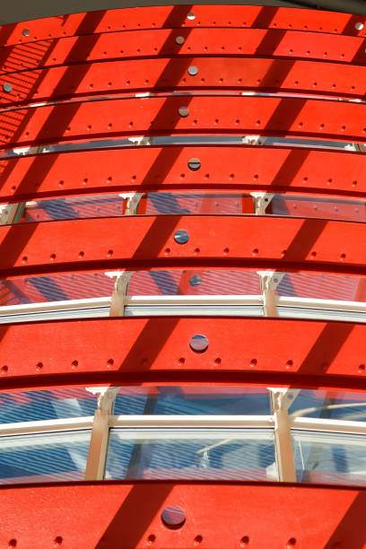 Gebogene Metallkonstruktionen mit leuchtend roter Farbe lackiert. Abbildung der Farb- und Designanwendung in der modernen Industrie. Vertikales Layout. – Foto