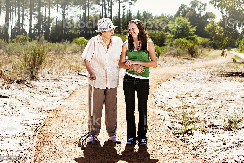 Bent old woman and young girl enjoy forest walk stock photo