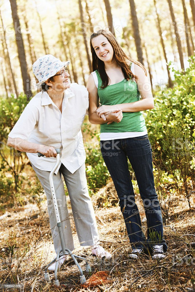 Bent old woman and young girl walk in forest stock photo