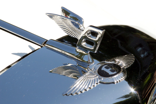 Bentley Badge And Hood Ornament In Sunlight Closeup Stock Photo - Download Image Now