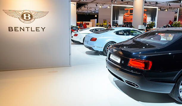 Bentley British luxury automaker motor show stand Amsterdam, The Netherlands - April 16, 2015: Bentley Flying Spur luxury limousine car, Bentley Continental GT V8S sports car and Bentley Continental GT3 racing car on display during the 2015 Amsterdam motor show. People in the background are looking at the cars. vehicle brand name stock pictures, royalty-free photos & images