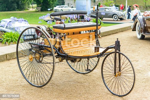Jüchen, Germany - August 5, 2016: Benz Patent Motor-wagen 1886 the world's first automobile - a vehicle designed to be propelled by an internal combustion engine. The car is on display during the 2016 Classic Days at castle Dyck. The car is displayed in a park, with people looking at the cars in the background.