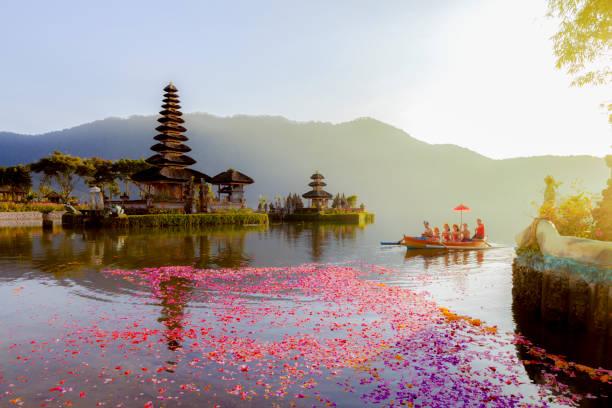 beratan lake in bali indonesia,  6 march 2017 : balinese villagers participating in traditional religious hindu procession in ulun danu temple beratan lake in bali indonesia - bali stockfoto's en -beelden