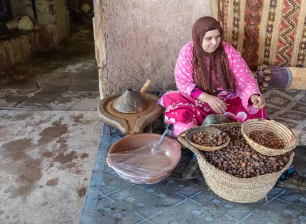 Berber women making Argon Oil in co-operative in Morocco stock photo
