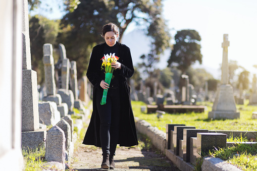 Bereaved young woman in black taking flowers to grave