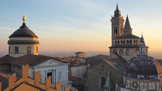 Bergamo, Italy. The old town. Aerial view of the Basilica of Santa Maria Maggiore and the dome of the cathedral during the sunset. In the background the Po plain