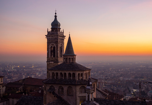 Bergamo, Italy. The old town. Amazing aerial view of the Basilica of Santa Maria Maggiore during the sunset. In the background the Po plain. Warm colors