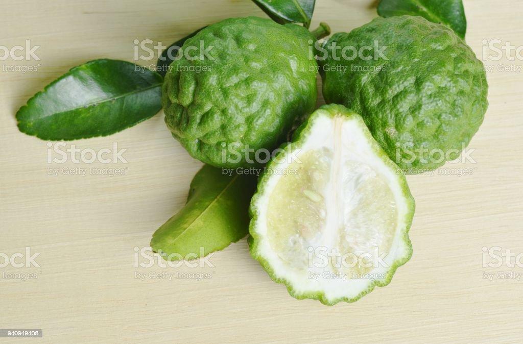 Fruit de bergamote avec feuilles isolées sur planche de bois - Photo