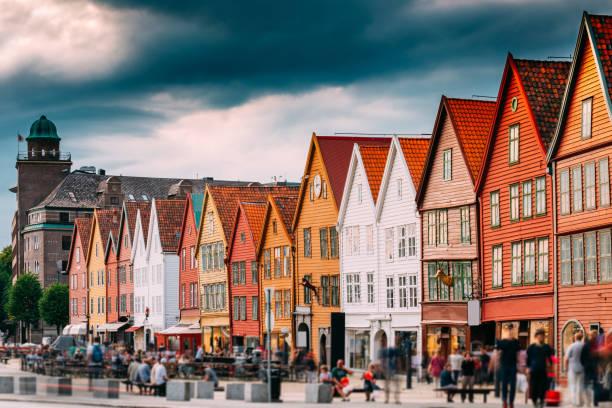 Bergen, Norway. Tourists People Visiting Historical Landmark Houses In Bryggen - Hanseatic Wharf In Bergen, Norway. UNESCO World Heritage Site. Famous Landmark stock photo