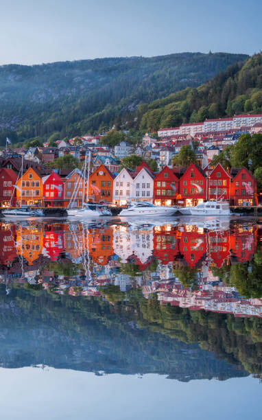 bergen street at night with boats in norway, unesco world heritage site - fjord stock photos and pictures