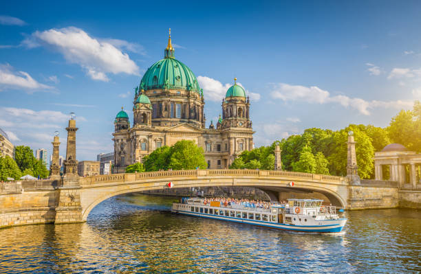 Berlin Cathedral with ship on Spree river at sunset, Berlin, Germany Beautiful view of historic Berlin Cathedral (Berliner Dom) at famous Museum Island with ship passing Friedrichsbrucke bridge on Spree river in golden evening light at sunset in summer, Berlin, Germany berlin stock pictures, royalty-free photos & images
