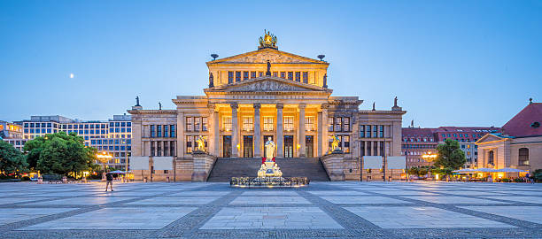 Berlin Concert Hall at Gendarmenmarkt square panorama at dusk, Berlin Panoramic view of famous Gendarmenmarkt square with Berlin Concert Hall in twilight during blue hour at dusk, Berlin Mitte district, Germany. gendarmenmarkt stock pictures, royalty-free photos & images