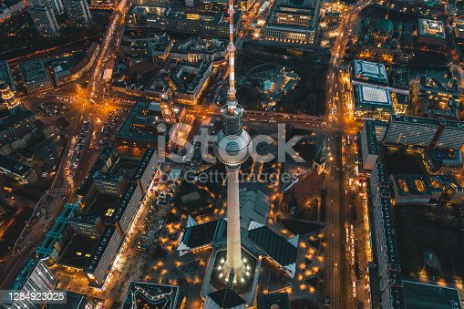 istock Berlin, Germany Alexanderplatz TV Tower after Sunset at Dusk with beautiful lit up Streets in orange lights of a Big City Cityscape, Aerial View 1284923025