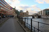 Berlin, Germany - January 2, 2019: City view in Berlin-Mitte. Promenade along the Spree river, far in the background the German parliament building. Europe.