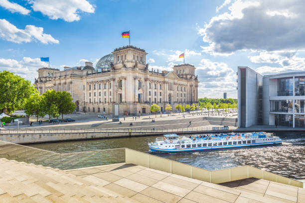Berlin government district with Reichstag and ship on Spree river in summer, Berlin Mitte, Germany Panoramic view of Berlin government district with excursion boat on Spree river passing famous Reichstag building and Paul Lobe Haus on a sunny day with blue sky and clouds, Berlin Mitte, Germany cupola stock pictures, royalty-free photos & images
