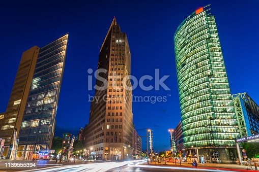 Chrome blue dusk sky framing the modern skyscrapers and busy highways of Potsdamer Platz, the iconic redeveloped square in the heart of Berlin, Germany's vibrant capital city.