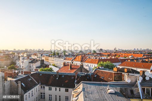 View of the Berlin panorama from the rooftop of Neukolln. Old buildings as well as the city centre with the famous Television Tower landmark can be seen, under the bright and clear sky.