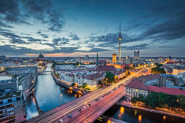 Berlin skyline with TV tower at night, Germany Aerial view of Berlin skyline with dramatic clouds in twilight during blue hour at dusk, Germany berlin stock pictures, royalty-free photos & images