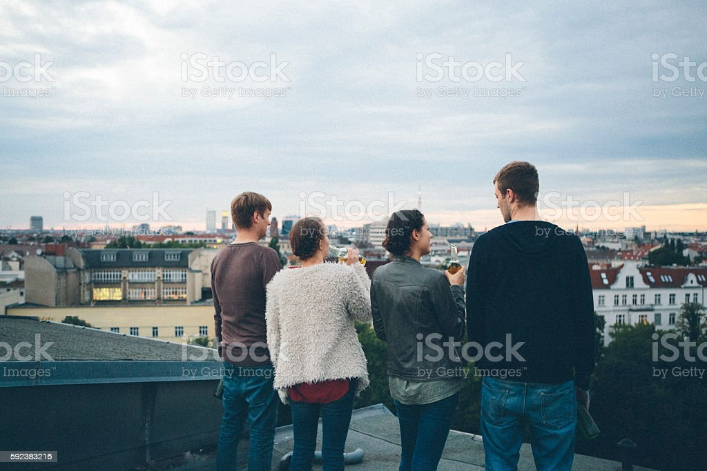 Berlin: small group, young adults on rooftop, talking, drinking beer stock photo