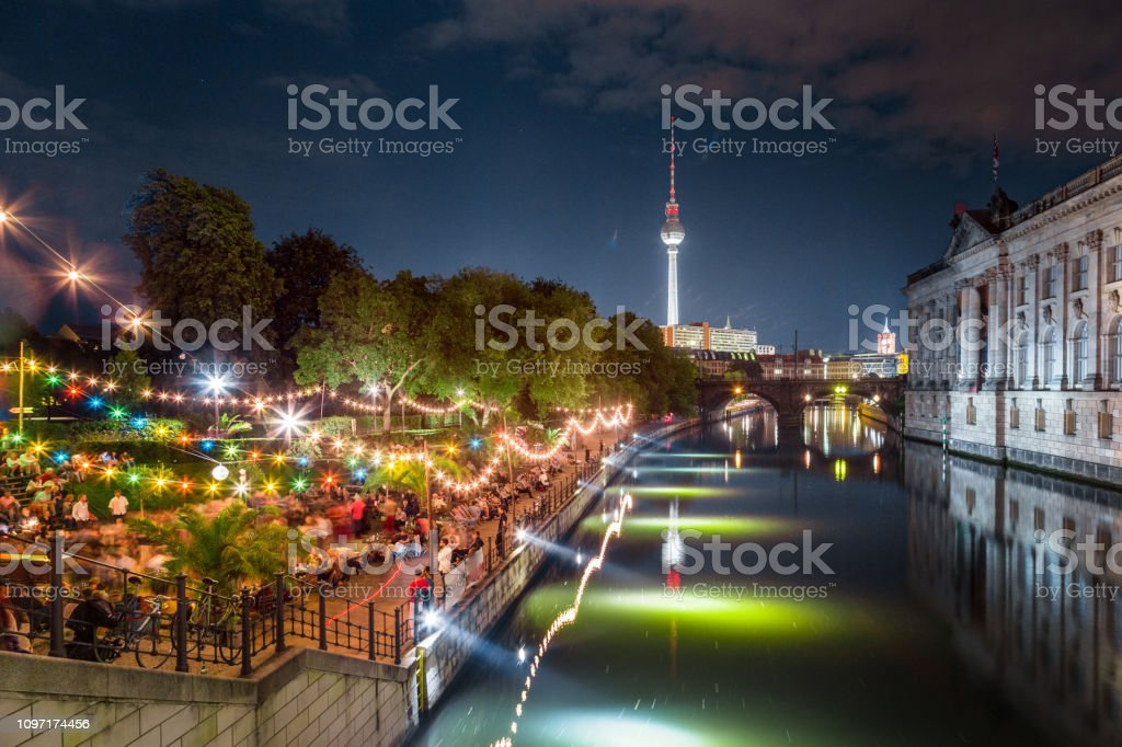 People dancing at summer Strandbar beach party near Spree river at...
