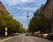 Berlin TV tower around one of streets in Berlin, Germany. Cars on the road, traffic. There are trees around the road. Berlin TV tower is behind the street covered trees. Horizontal composition. Close to Alexanderplatz in Berlin-Mitte, the tower was constructed between 1965 and 1969 by the administration of the German Democratic Republic. It was intended as a symbol of Berlin, which it remains today, as it is easily visible throughout the central and some suburban districts of Berlin. With its height of 368 meters, it is the tallest structure in Germany, and the second tallest structure in the European Union.