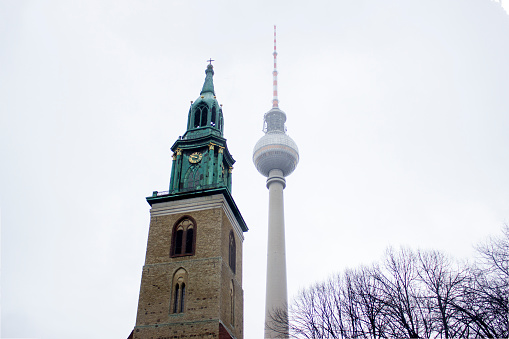 Berlin TV tower with St. Mary's Church in foggy day