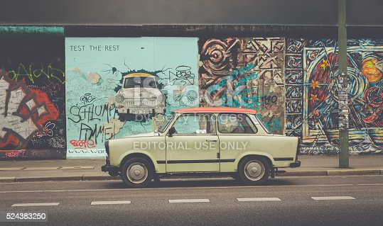 Berlin, Germany - July 12, 2015: Famous Berliner Mauer (Berlin Wall) at East Side Gallery with an old Trabant, the most common vehicle used in East Germany, in front, Berlin Friedrichshain-Kreuzberg, Germany.