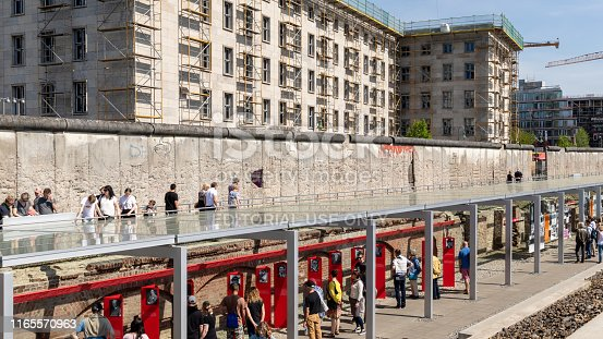 Berlin, Germany - April 28, 2018: Tourists walking past a part of the Berlin Wall at the Topography of Terror Documentation Center.