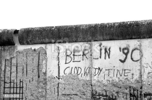 A black and white photo of Berlin wall with graffiti.