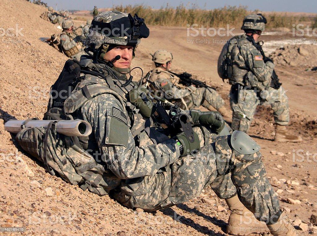 Berm Break U.S. Soldier takes a break on a berm during patrol in Ramadi, Iraq.  Adult Stock Photo