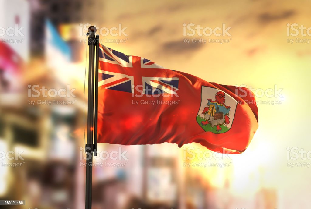 Bermuda Flag Against City Blurred Background At Sunrise Backlight stock photo
