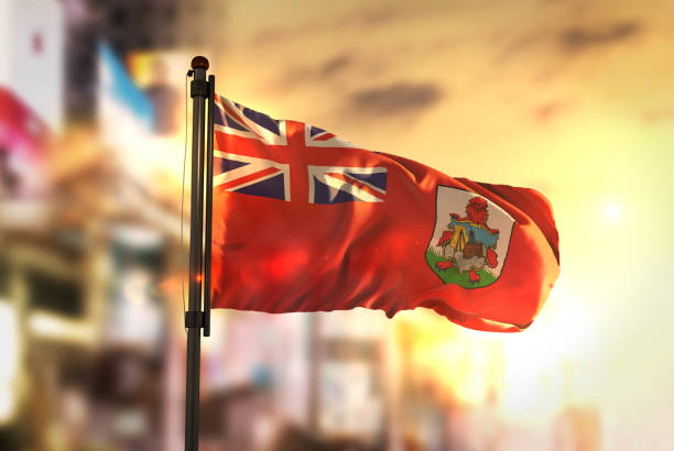 Bermuda Flag Against City Blurred Background At Sunrise Backlight stock photo
