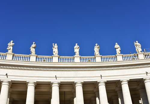 Bernini's Colonnade and statues at St. Peter's Square with blue sky. Vatican City, Rome, Italy.