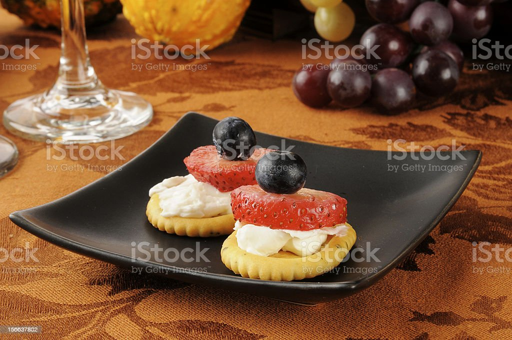 Berries and ream cheese on crackers royalty-free stock photo