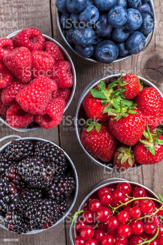 Berries closeup assortment in tin cans overhead on wooden table stock photo